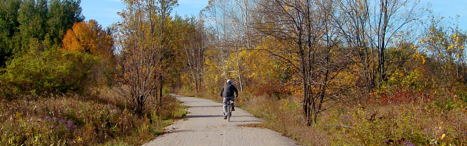 Man riding bike on trail in the fall