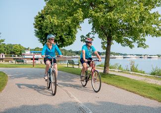 Two people cycling at waterfront