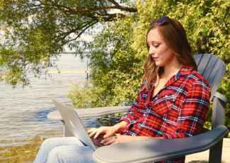 Girl on dock with laptop