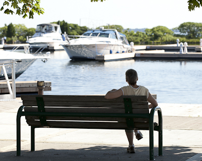 man sitting on bench looking at port of orillia