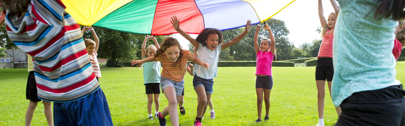 Children playing with parachute at camp