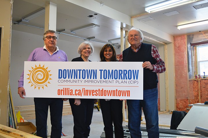 "Councillors Ralph Cipolla, Ted Emond and Pat Hehn pictured with Downtown Tomorrow Community Improvement Plan grant recipient Kathleen Philip. They hold a sign that says ""Downtown Tomorrow Community Improvement Plan (CIP) orillia.ca/investdowntown"
