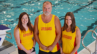 Lifeguards standing in front of pool
